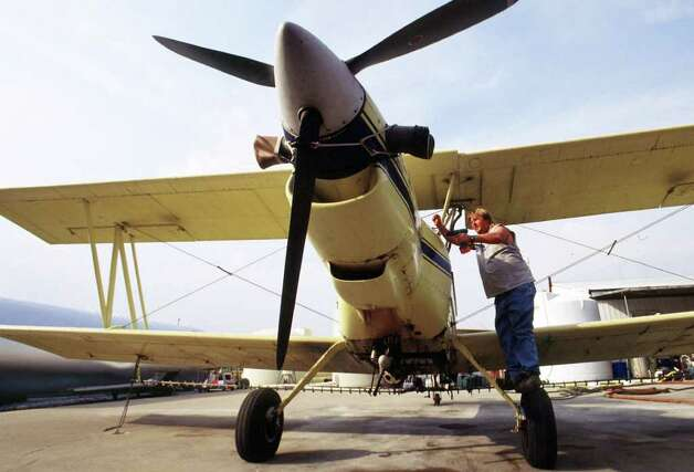 FILE - In this Monday, Sept. 17, 2001 file picture, Robert Williams of Mihand Aircraft near England, Ark., places the engine cover back on his agricultural airplane after removing the battery cable. Federal officials allowed crop-spraying planes to return to the skies as long as they stayed away from commercial airports, one day after they were grounded because of security concerns after the previous week's terrorist attacks. On Friday, Sept. 2, 2011, the FBI and Homeland Security have issued a nationwide warning about al-Qaida threats to small airplanes, just days before the anniversary of the 2001 terrorist attacks. (AP Photo/Spencer Tirey, File) Photo: Spencer Tirey