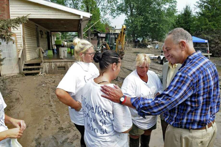 U.S. Sen. Chuck Schumer, right, and U.S. Rep. Paul Tonko, partially obscured second from right,  encourage Renee Wolbert, second from left, her sister Lindsay, left, and their mother Donna Wolbert, third from left, after touring their flood devastated home following last Sunday's Tropical Storm Irene, on Sunday Sept. 4, 2011, in Rotterdam Junction, NY.  (Philip Kamrass / Times Union) Photo: Philip Kamrass / 00014510A