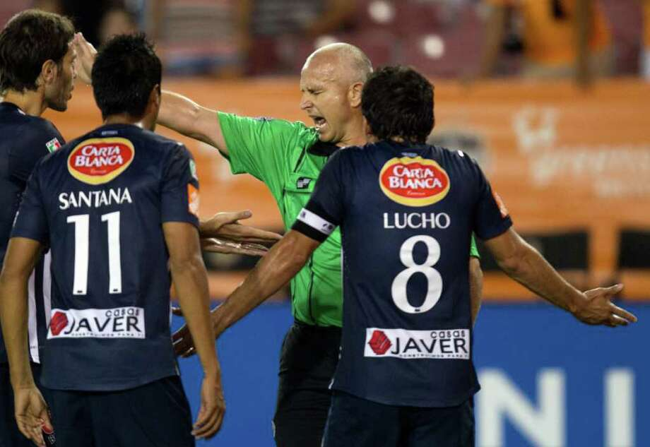 Referee Jasen Anno shouts at CF Monterrey players contesting a penalty call during the first half. Photo: Smiley N. Pool, Houston Chronicle / © 2011  Houston Chronicle