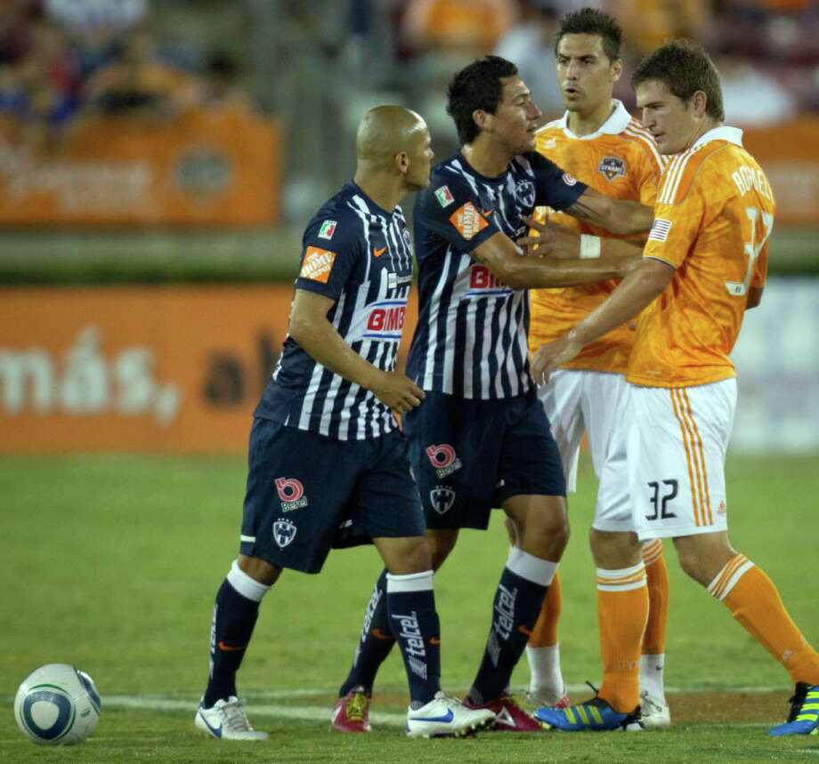 Dynamo players Bobby Boswell (32) and Geoff Cameron get into a shoving match with CF Monterrey's Dario Carreno, center, and Humberto Suazo, far left, during the first half. Photo: Smiley N. Pool, Houston Chronicle / © 2011  Houston Chronicle