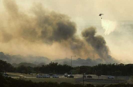 A helicopter dumps water on a fire in Steiner Ranch, west of Austin, Texas, on Sunday Sept. 4, 2011. (AP Photo/Austin American-Statesman, Jay Janner) Photo: Jay Janner, MBR / Austin American-Statesman