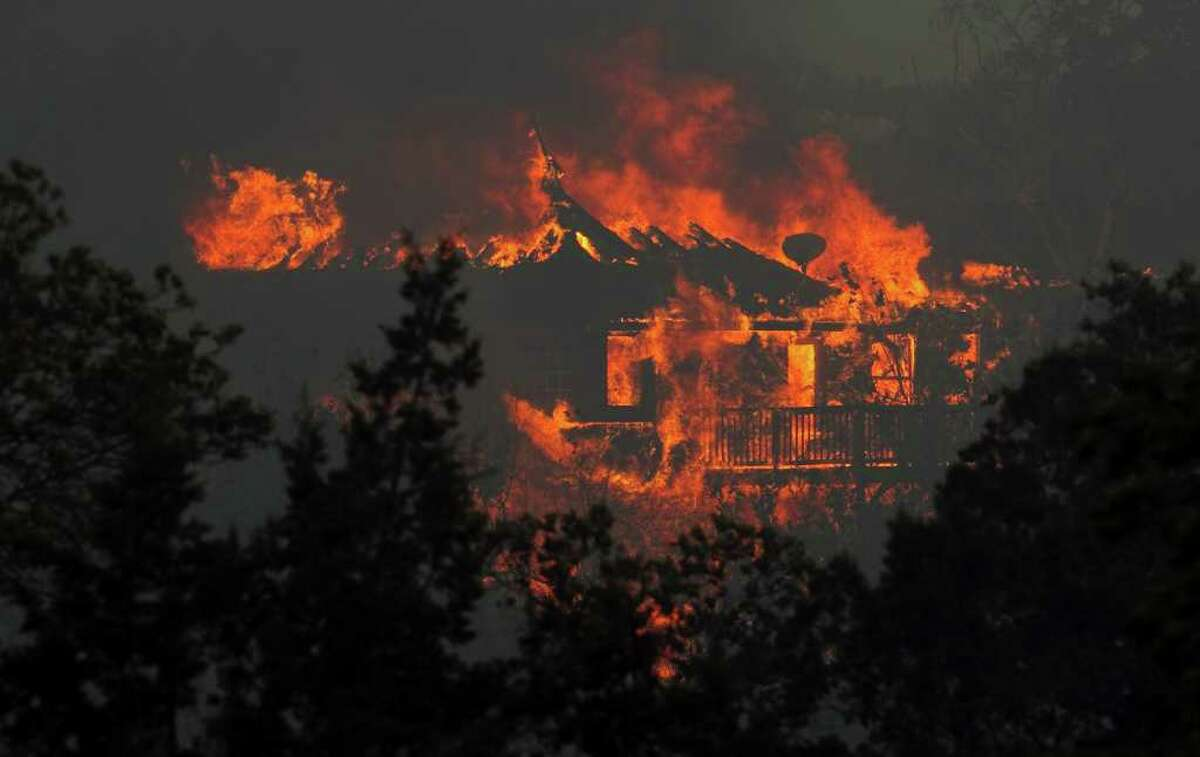 A fire burns a home in Steiner Ranch west of Austin, Texas, on Sunday afternoon, Sept. 4, 2011. The fires are forcing evacuations in Pflugerville, Steiner Ranch and Bastrop County. (AP Photo/Austin American-Statesman, Jay Janner) MAGS OUT; NO SALES; TV OUT; INTERNET OUT; AP MEMBERS ONLY
