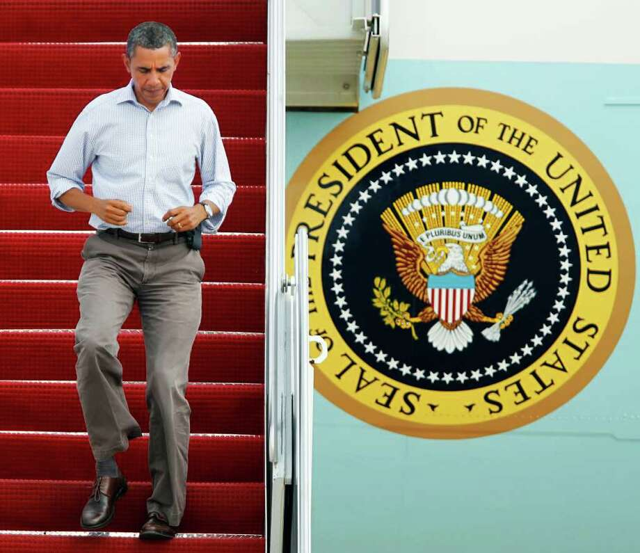 President Barack Obama jogs down the ramp of Air force One as he arrives at Andrews Air Force Base, Md., after a trip to New Jersey to tour Hurricane Irene damage, Sunday, Sept. 4, 2011.   (AP Photo/Manuel Balce Ceneta) Photo: Manuel Balce Ceneta, STF / AP