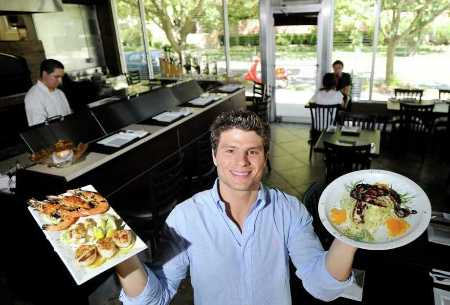 Louis Barresi, owner of Doppio Artisan Pizza & Gelato, holds a plate of Grigliata Di Pebce (three head of shrimp, calamari and scallops) at left, and a plate of Polpo Grigliato (char-grilled octopus, fennel and citrus) at right, in his restaurant at 41 East Elm Street, Greenwich, Friday, Aug. 12, 2011. Photo: Bob Luckey / Greenwich Time