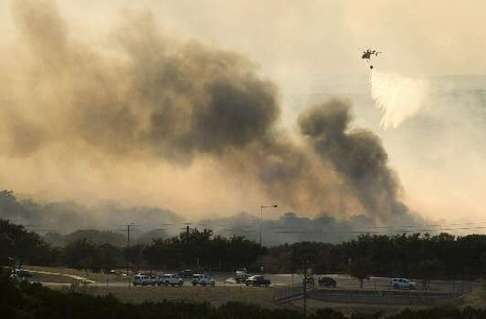 A helicopter dumps water on a fire in Steiner Ranch, west of Austin, Texas, on Sunday Sept. 4, 2011. Firefighters battled fires across Central Texas, forcing evacuations in Pflugerville, Steiner Ranch and Bastrop County.