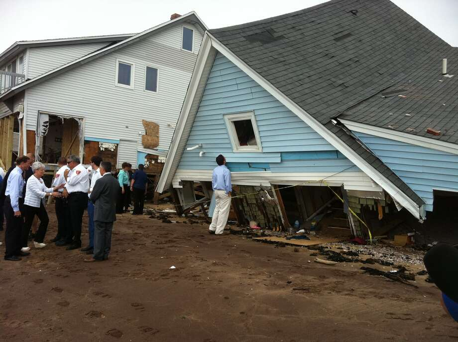 Gov. Dannel P. Malloy looks into the window of a home ruined in last week's tropical storm during a tour of the area on Monday, Sept.5, 2011.