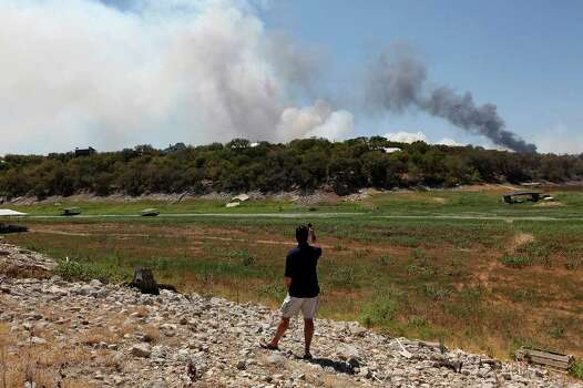 Mark Adams, of Austin, takes a picture of a wildfire in the Paleface Ranch area off State Highway 71 near Spicewood, Texas, Monday, Sept. 5, 2011. Adams was trying to get to a house he owns in Marble Falls, Texas but was diverted to the closure of SH71. JERRY LARA/glara@express-news.net Photo: JERRY LARA, JERRY LARA/glara@express-news.net / SAN ANTONIO EXPRESS-NEWS
