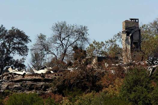 The remains of a house destroyed by a wildfire in the Paleface Rancharea off State Highway 71 near Spicewood, Texas, are seen on a bluff, Monday, Sept. 5, 2011. JERRY LARA/glara@express-news.net Photo: JERRY LARA, JERRY LARA/glara@express-news.net / SAN ANTONIO EXPRESS-NEWS