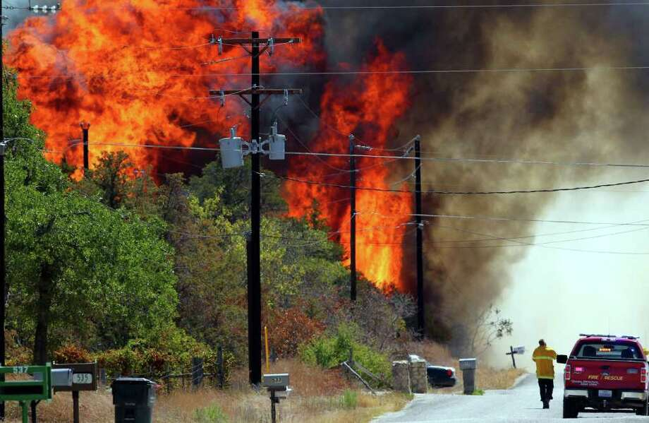 Fire rages on Leisure lane in a neighborhood near the west end of Bastrop, Texas off Highway 71 Monday September 5, 2011. Fires have been burning through many areas in central Texas as authorities try to gain control of the blazes. Photo: JOHN DAVENPORT, JOHN DAVENPORT/jdavenport@express-news.net / SAN ANTONIO EXPRESS-NEWS (Photo can be sold to the public)