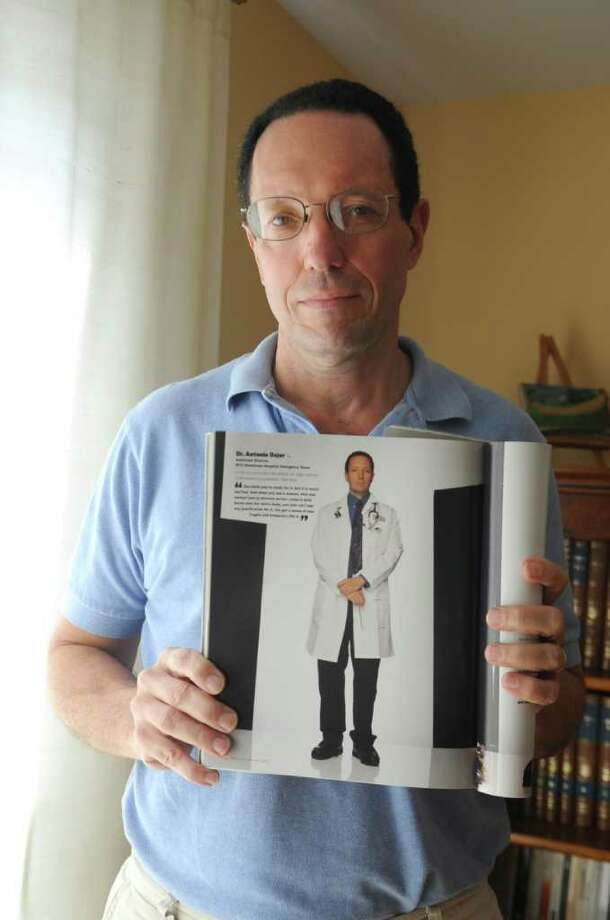 "Dr. Tony Dajer works at the emergency room at New York Downtown Hospital in New York City and he worked on 9/11.  His picture was printed in Life's ""In the land of the Free September 11-and After.""  He holds his photograph at home in Riverside on Monday, Sept. 5, 2011. Photo: Helen Neafsey / Greenwich Time"
