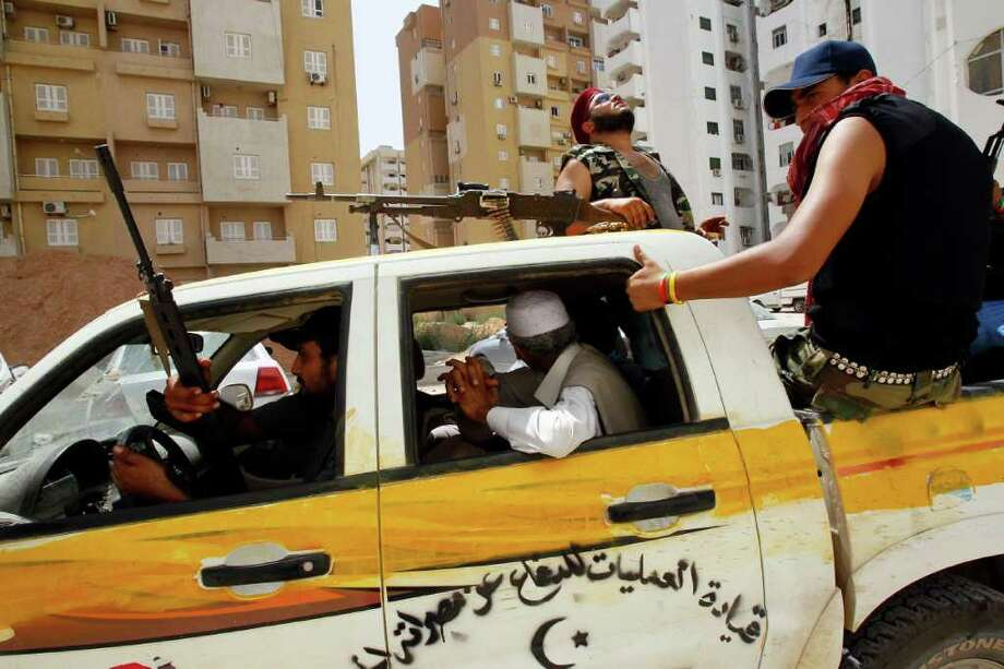 FRANCOIS MORI : ASSOCIATED PRESS IN CUSTODY: A Tripoli resident in the back of a pickup hides his face after being arrested by Libyan rebels for possession of weapons provided by ousted leader Moammar Gadhafi. Photo: Francois Mori, STF / AP