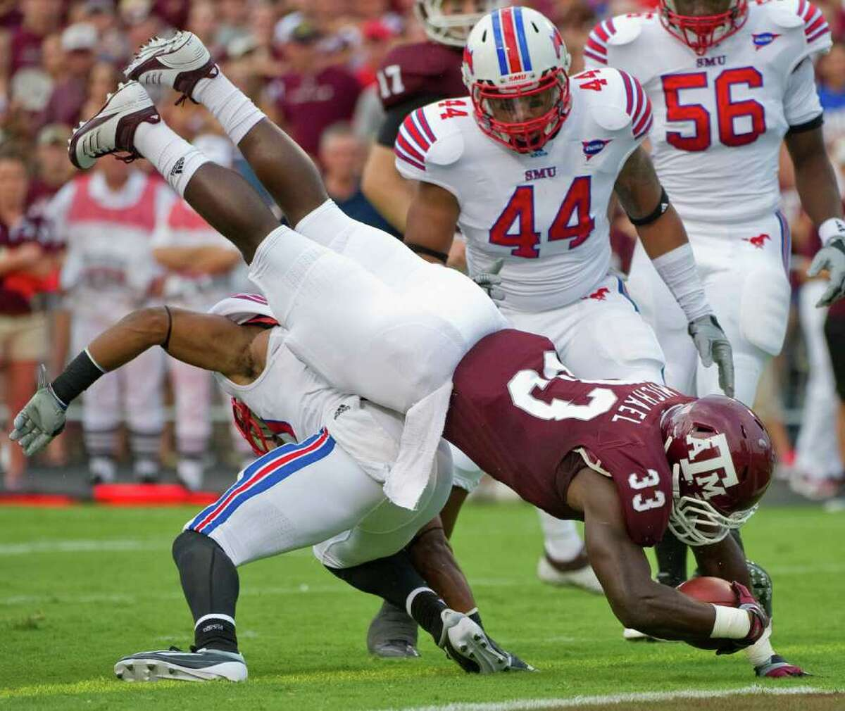 Texas A&M running back Christine Michael (33), a West Brook grad, dives over SMU's Ryan Smith, bottom, as Taylor Reed (44), also a West Brook grad, helps during the first quarter of Sunday's game in College Station. (AP Photo/Dave Einsel)