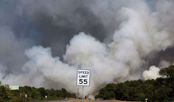 Smoke encroaches on Highway 71 in Bastrop, Texas Monday September 5, 2011 as wildfires continue to burn in the area. Photo: JOHN DAVENPORT, Express-News / SAN ANTONIO EXPRESS-NEWS (Photo can be sold to the public)