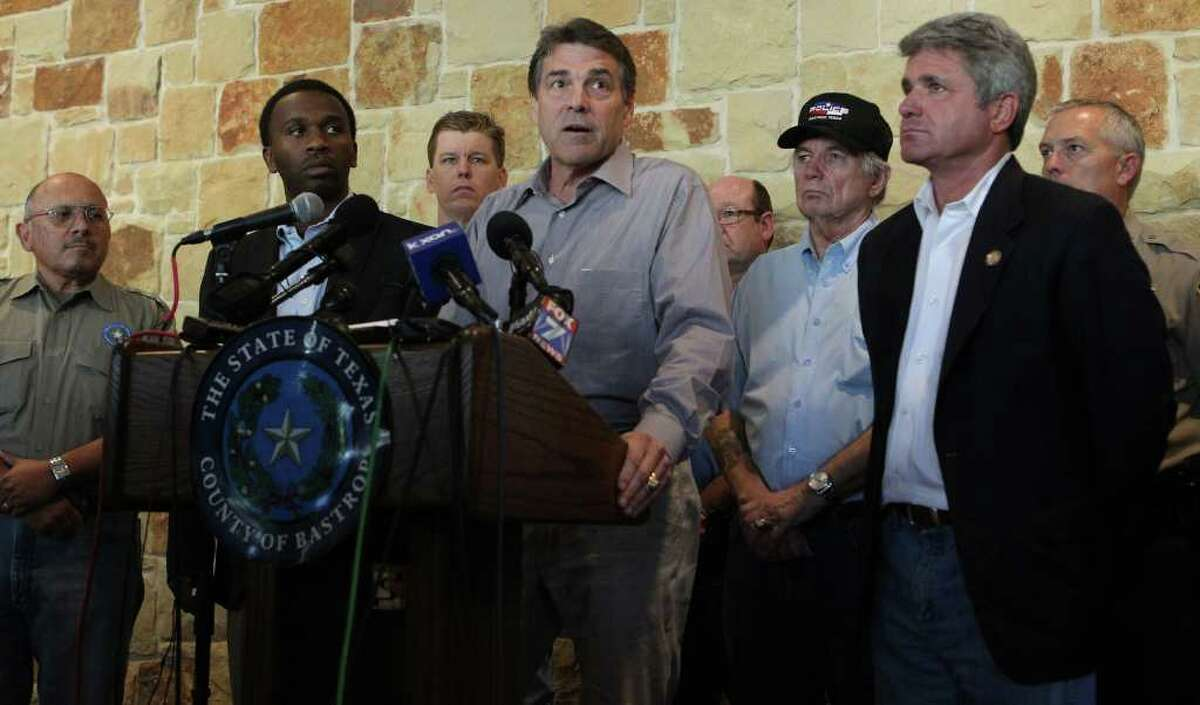 Texas Governor Rick Perry (at lectern) speaks to the media, citzens and first responders during a press conference held at the Bastrop Convention Center Monday September 5, 2011. Perry spoke about wildfires in the area and ecouraged Texans to work together.