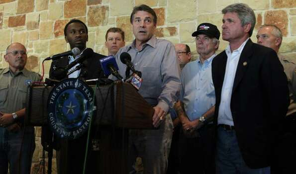 Texas Governor Rick Perry (at lectern) speaks to the media, citzens and first responders during a press conference held at the Bastrop Convention Center Monday September 5, 2011. Perry spoke about wildfires in the area and ecouraged Texans to work together. Photo: JOHN DAVENPORT, Express-News / SAN ANTONIO EXPRESS-NEWS (Photo can be sold to the public)