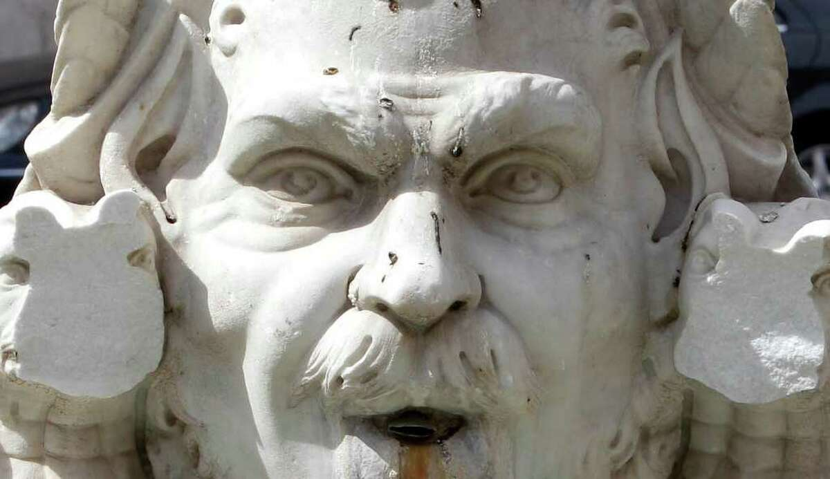 FILE - In this Sunday, Sept. 4, 2011 file photo two chunks of marble are missing from the Moor fountain in Rome's Piazza Navona Sunday, Sept. 4, 2011. Police said Monday they have detained the alleged vandal who knocked two chunks of marble off a statue in Rome's famed Piazza Navona. Rome Mayor Gianni Alemanno pledged no clemency for the man, saying Italy must protect and defend its artistic treasures. Security camera footage showed the man climbing in the fountain early Saturday and repeatedly attacking the statue, one of four large faces at the edge of the fountain, with a large rock. The damaged Moro Fountain, however, was a 19th-century copy. (AP Photo/Pier Paolo Cito, File)