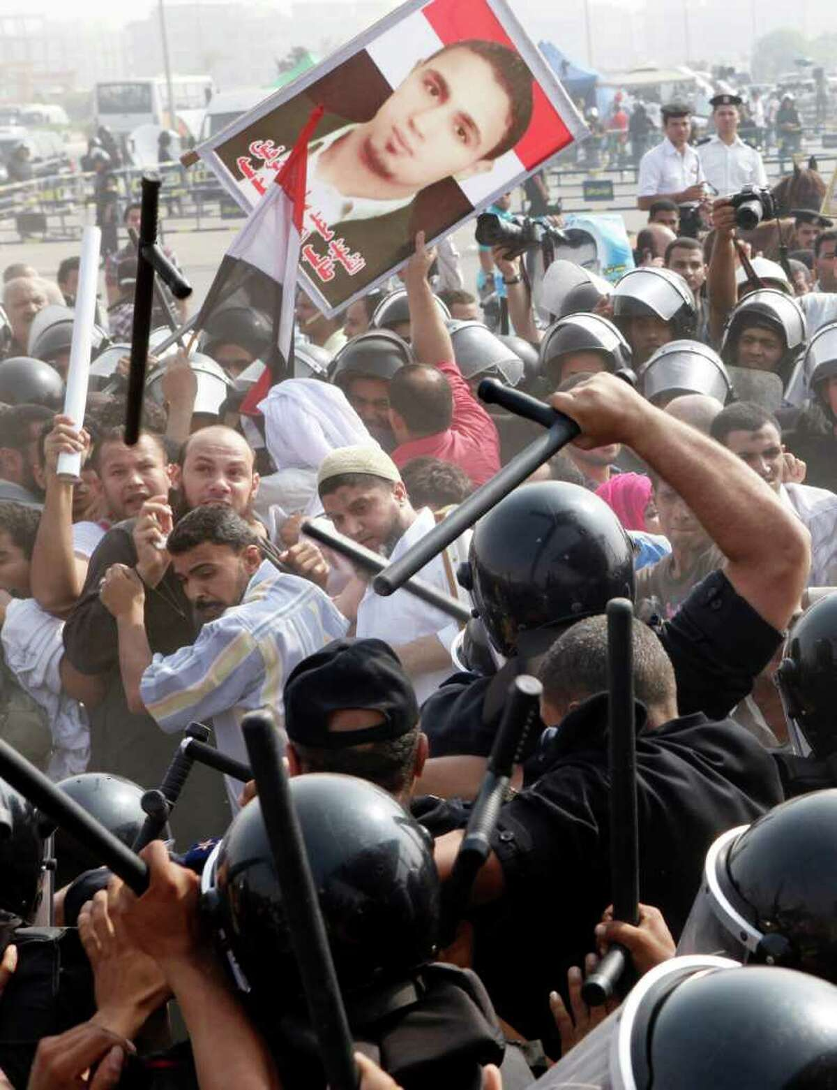 Egyptian anti-Mubarak protesters flee from clashes with riot policemen outside police academy court in Cairo, Egypt, Monday, Sept. 5, 2011. Mubarak, his two sons Alaa and Gamal, his security chief Habib el-Adly and six top police officers face their third session of trial, on charges they ordered the use of lethal force against protesters during Egypt's 18-day uprising, when some 850 protesters were killed. Poster at center showing one of the killed protesters. (AP Photo/Amr Nabil)