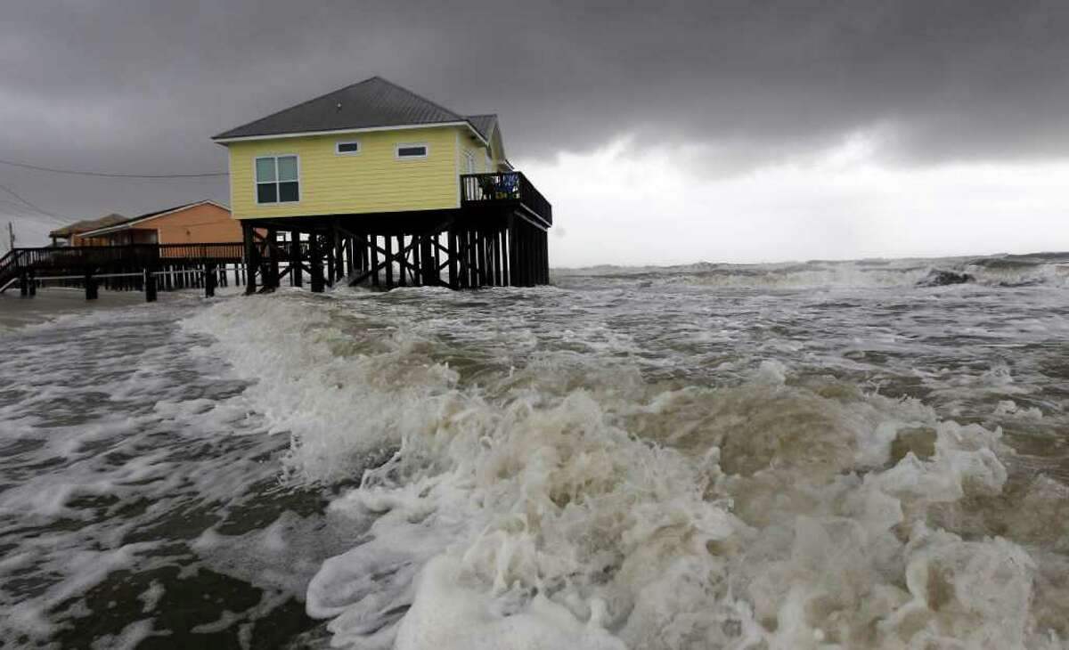 Squalls and heavy surf pounds homes along the beach in Dauphin Island, Ala., Monday, Sept. 5, 2011. The heavy waves were breaking under homes, damaging underpinnings and ripping porches and steps from the structures. Tropical Storm Lee is moving inland along the Gulf Coast bringing torrential rains and flooding. (AP Photo/Dave Martin)