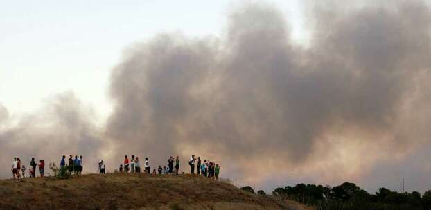 A large plume of smoke rises from a wildfire at onlookers watch from a hill, Monday, Sept. 5, 2011, in Bastrop, Texas.  A roaring wildfire raced unchecked Monday through rain-starved farm and ranchland in Texas, destroying nearly 500 homes during a rapid advance fanned in part by howling winds from the remnants of Tropical Storm Lee. (AP Photo/Eric Gay) Photo: Eric Gay, Associated Press / AP