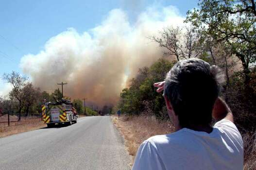 Local resident George Harris looks on from a safe distance as firefighters attempt to control a blaze in Cedar Park, Texas  on Monday, Sept. 5, 2011.  A roaring wildfire raced unchecked Monday through rain-starved farm and ranchland in Texas, destroying nearly 500 homes during a rapid advance fanned in part by howling winds from the remnants of Tropical Storm Lee.   (AP Photo/The Daily Texan, Thomas Allison) Photo: Thomas Allison, Associated Press / Thomas Allison
