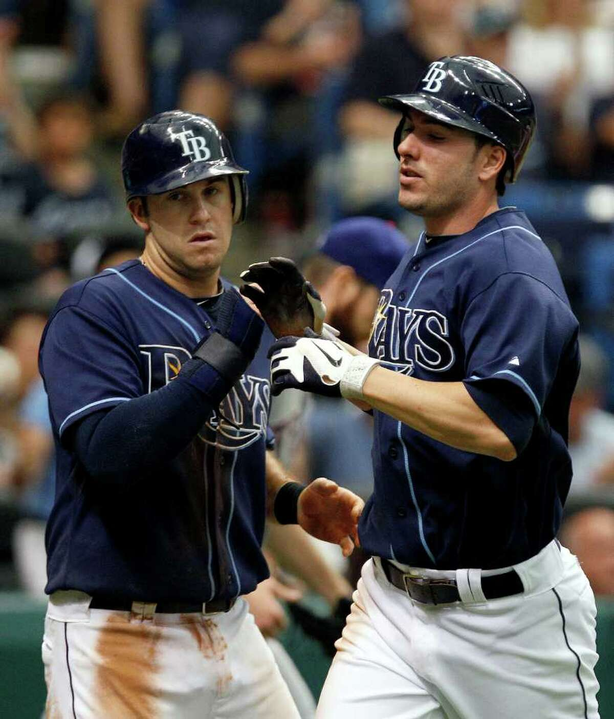 Tampa Bay Rays' Matt Joyce, right, and teammate Evan Longoria celebrate after scoring on a two run single by Casey Kotchman off Texas Rangers starting pitcher Scott Feldman during the fourth inning of a baseball game Monday, Sept. 5, 2011, in St. Petersburg, Fla.