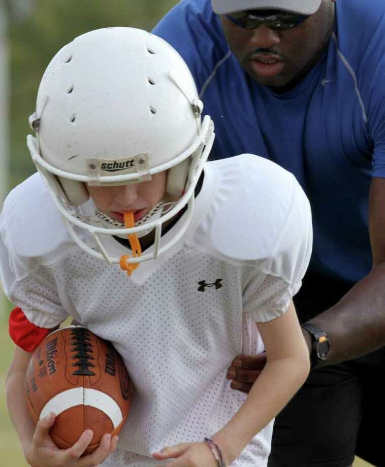 Thomas B. Shea: For the Chronicle GUIDANCE: Coach Henry Davis helps a fifth-grader with his form during a running drill at a talent evaluation session for the Southwest Football League. Photo: For The Chronicle:  Thomas B. Sh, Thomas B. Shea