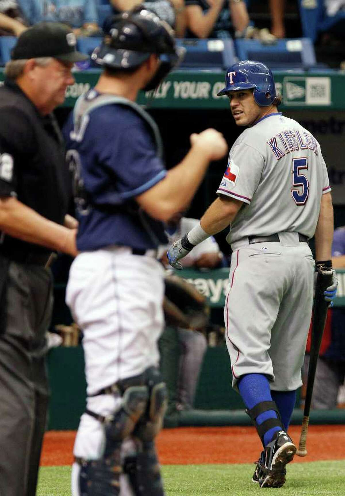 Texas Rangers' Ian Kinsler (5) has words with home plate umpire Joe West, left, after being called out on strikes on pitch from Tampa Bay Rays' James Shields during the third inning of a baseball game Monday, Sept. 5, 2011, in St. Petersburg, Fla. Looking on is Rays' catcher John Jaso.
