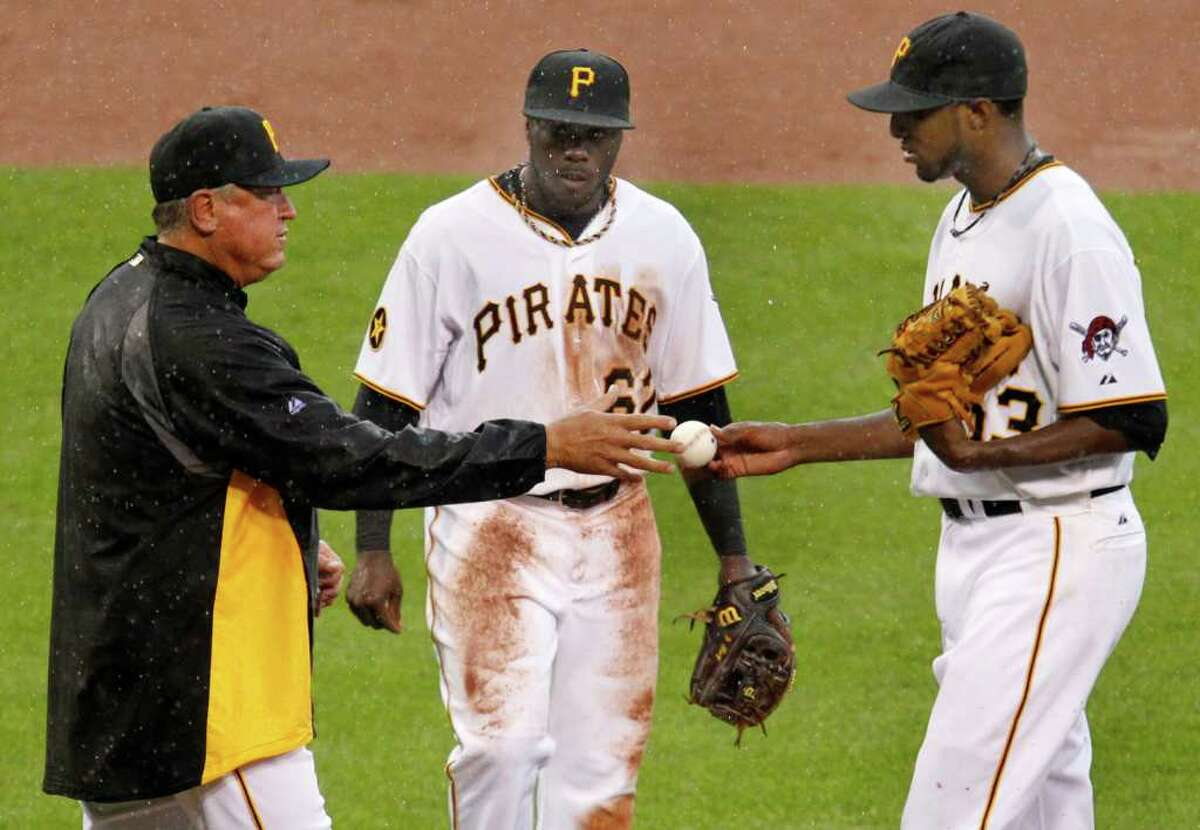 Pittsburgh Pirates pitcher James McDonald, right, hands the ball to manager Clint Hurdle, left, in front of third baseman Josh Harrison as he leaves the game after pitching into the eighth inning of a baseball game against the Houston Astros in Pittsburgh, Monday, Sept. 5, 2011. The Pirates won 3-1, with McDonald getting the win.