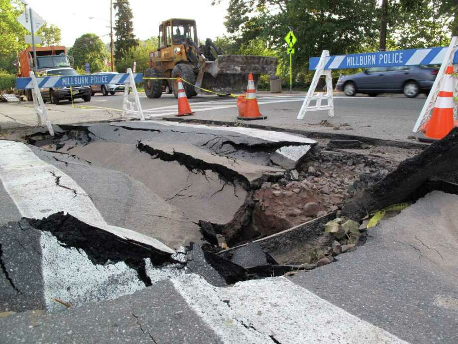 In this Sept. 2, 2011 photo, a front loader passes a sink hole in a Millburn, N.J. intersection. Officials say it could take months just to make basic repairs due to damage caused by Hurricane Irene. Many permanent fixes will have to wait until the spring. (AP Photo/Chris Hawley) Photo: Chris Hawley