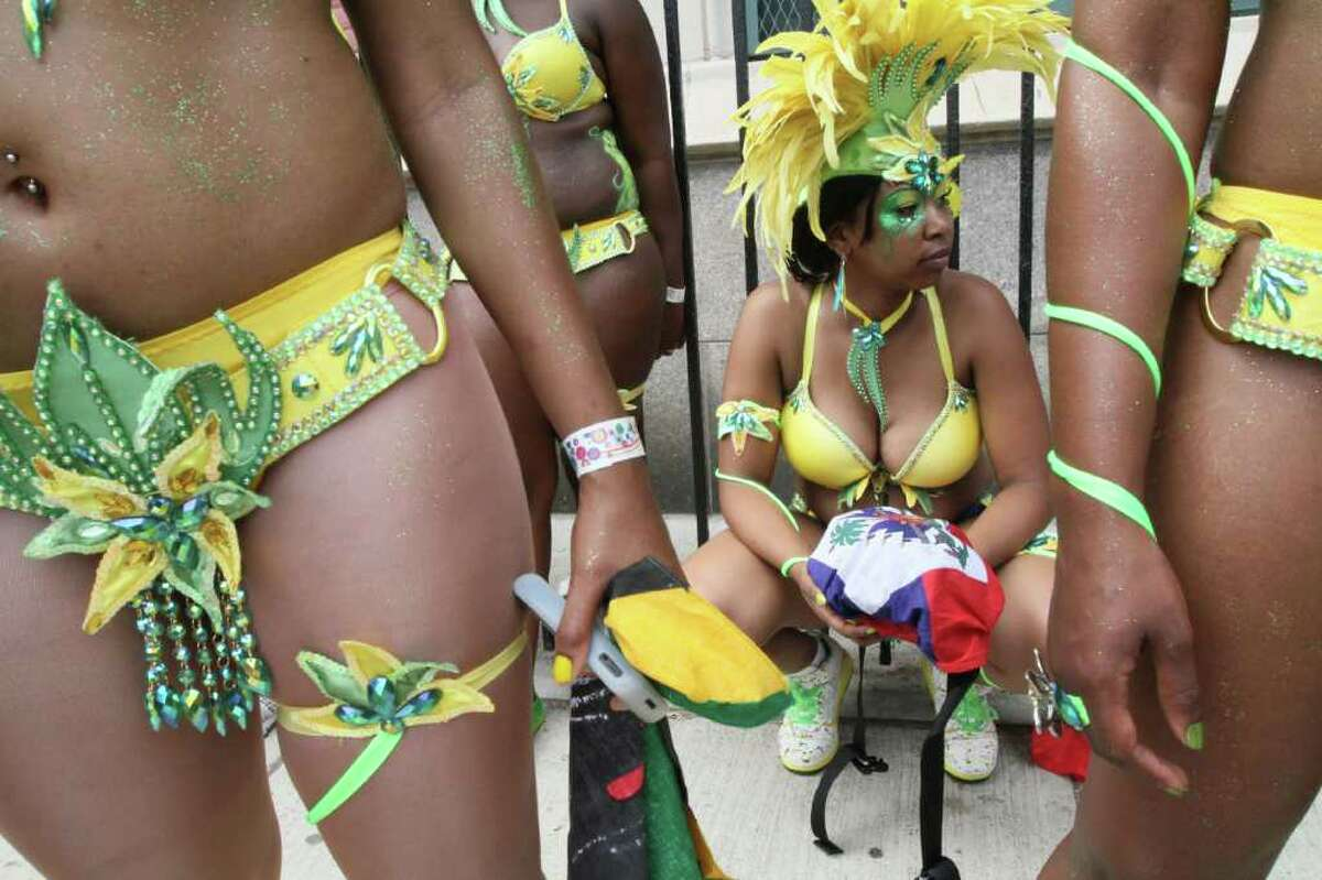 Dressed to take part in the festivities, Lisa Johnson, squatting, waits with others for the start of the West Indian Day Parade, Monday, Sept. 5, 2011, in the Brooklyn borough of New York. (AP Photo/Tina Fineberg)