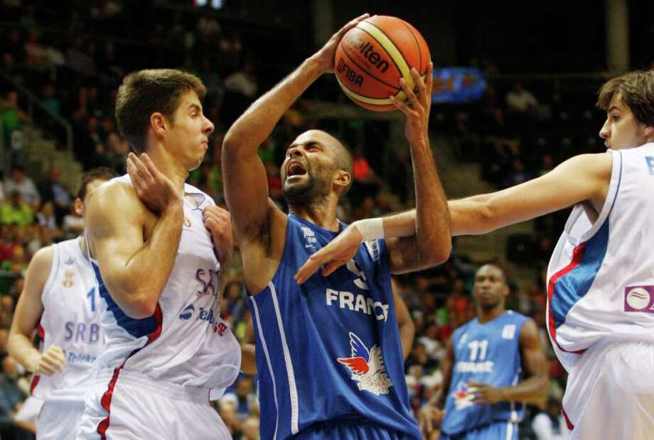 Milenko Tepic, left, and Nemanja Bjelica, right, from Serbia try to block Tony Parker, center, from France during the EuroBasket European Basketball Championship Group B match in Siauliai, Lithuania, Monday, Sept. 5, 2011. Photo: Petr David Josek/Associated Press / AP