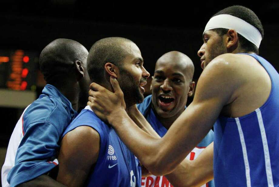Nicolas Batum, right, from France celebrates with his teammates Tony Parker, left, and Ali Traore, center, after defeating Serbia in the EuroBasket European Basketball Championship Group B match in Siauliai, Lithuania, Monday, Sept. 5, 2011. France won the match 97-96. Photo: Petr David Josek/Associated Press / AP