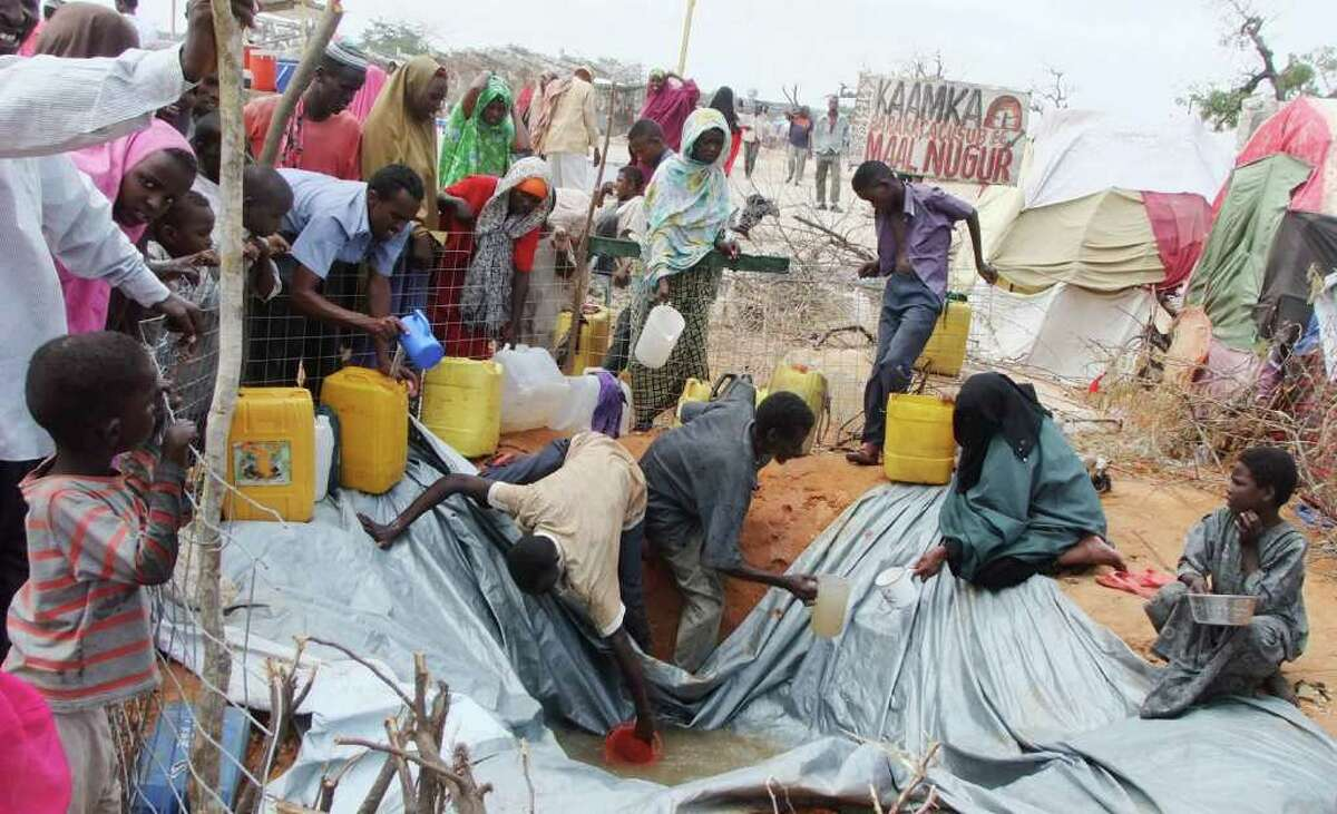 """Refugees from southern Somalia fill receptacles with rain water, at a refugee camp in Mogadishu Somalia, Monday, Sept. 5, 2011. Famine has spread into one more region of Somalia and hundreds of Somalis are dying every day, according to the United Nations. About 750,000 more people may die from famine in the next four months if there is no adequate response, the U.N. Food Security and Nutrition Analysis Unit for Somalia said, an increase of 66 percent from July. The top humanitarian official for the Somalia described getting aid to the starving as a """"race against time"""" and warned the famine would probably spread before the end of the year.(AP Photo/Farah Abdi Warsameh)"""