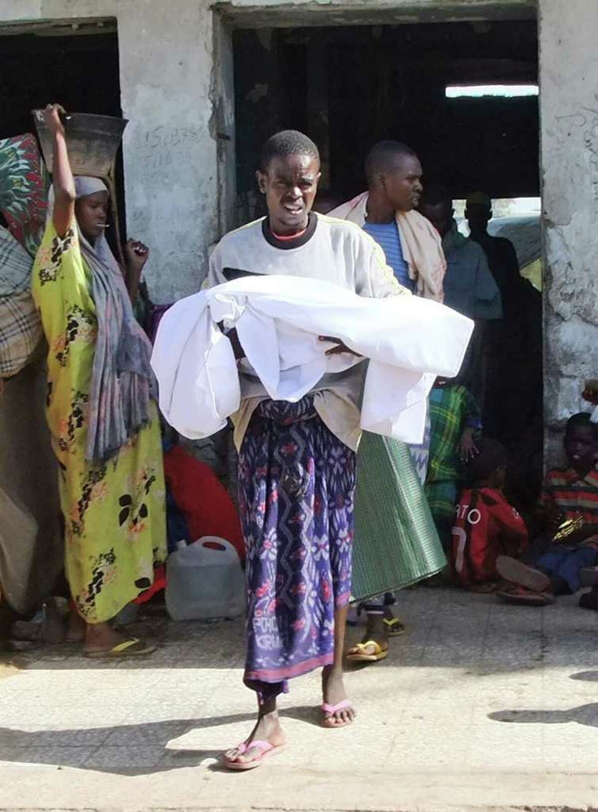 """A Southern Somali man carries his dead child in Mogadishu, Somalia, Monday, Sept. 5, 2011. Famine has spread into one more region of Somalia and hundreds of Somalis are dying every day, the United Nations said Monday, describing getting aid to the starving as a """"race against time"""" and warned the famine would probably spread before the end of the year. (AP Photo/Farah Abdi Warsameh)"""
