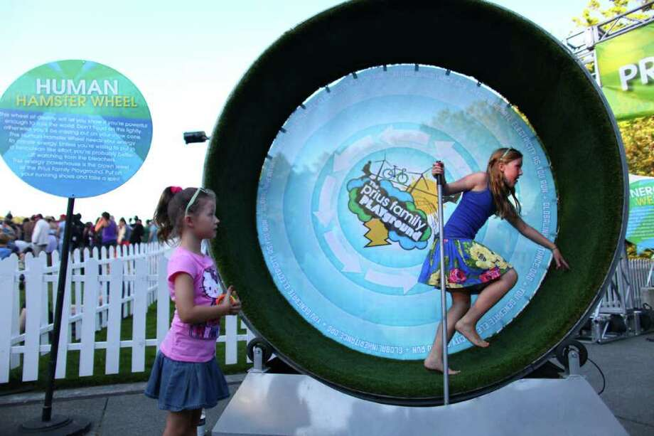 Clara Hopkins, 7, watches as her sister Elizabeth Hopkins, 10, runs inside a 'human hamster wheel,' part of a Toyota promotion booth. Photo: JOSHUA TRUJILLO / SEATTLEPI.COM