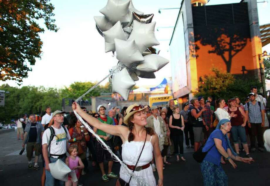 A performer with Orkestar Zirkonium dances with balloons as the band plays on the Seattle Center grounds. Photo: JOSHUA TRUJILLO / SEATTLEPI.COM
