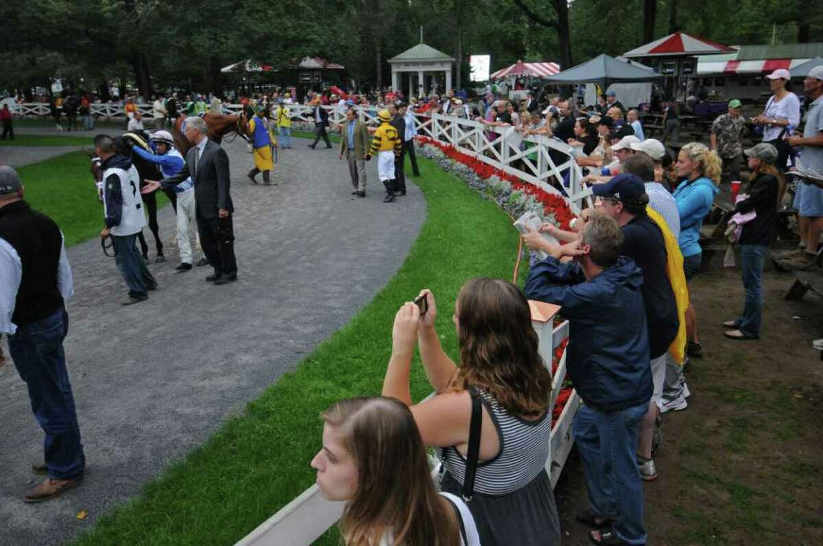 Race fans watch as trainer Todd Pletcher gestures while talking to jockey John Velazquez before getting on Hunt Crossing, as they leave the Paddock along with other horses for the start of The Three Chimneys Hopeful race on Monday Sept. 5, 2011 in Saratoga Springs, NY. (Philip Kamrass / Times Union)