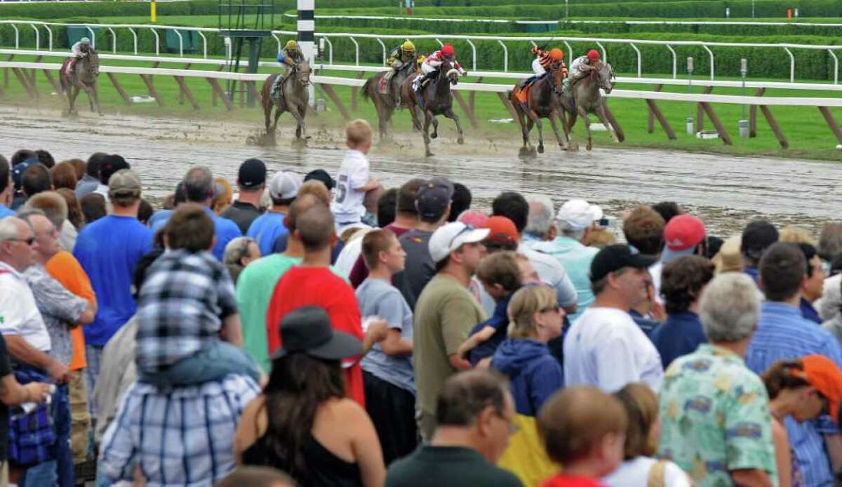 Race fans watch as jockey Eddie Castro aboard Tug of War, third from the right, heads to the finish line and victory in the sixth race at the Saratoga Race Course on Monday Sept. 5, 2011 in Saratoga Springs, NY. (Philip Kamrass / Times Union)