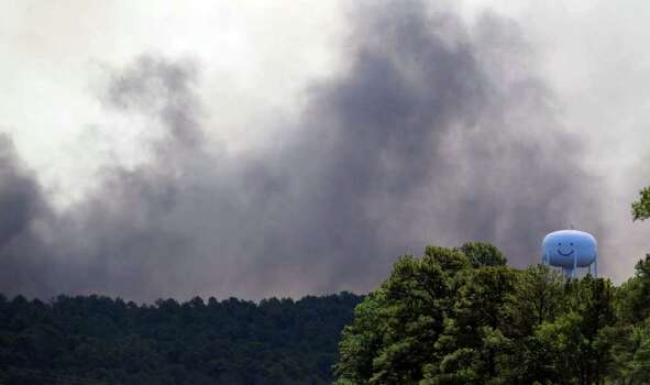 Smoke drifts across the sky and treelines near Bastrop as wildfires there still burn out of control, Sept. 5, 2011. Photo: Express-News