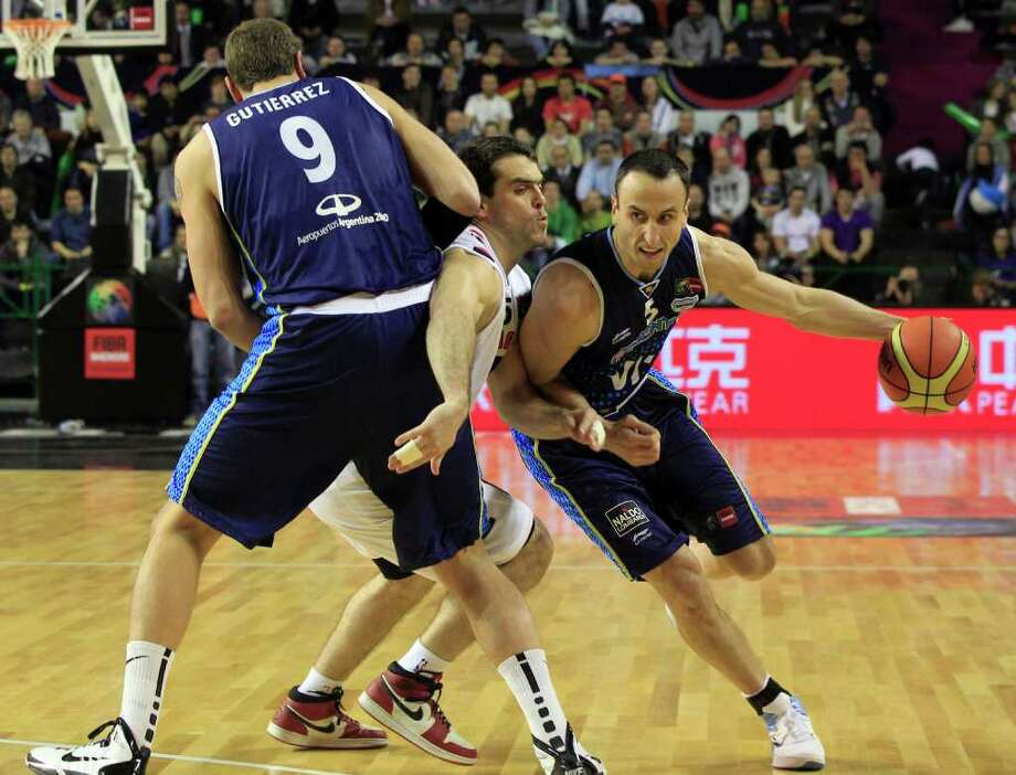 Argentina's Manu Ginobili, right, dribbles past Paraguay's Daniel Perez, center, as Juan Gutierrez, left, blocks during a FIBA Americas Championship basketball game in Mar del Plata, Argentina, Tuesday, Aug. 30, 2011. The top two finishers of the tournament get an automatic berth in the 2012 London Olympics and the next three advance to the last-chance Olympic qualifying tournament to be held in July 2012. Photo: Martin Mejia/Associated Press