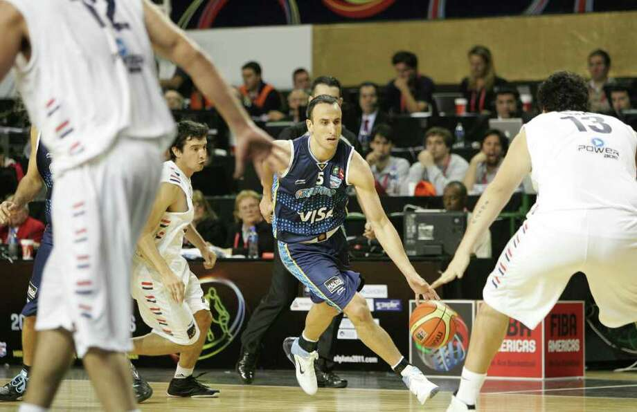 Manu Ginobili drives through a pack of Paraguay defenders on Tuesday, Aug. 30, 2011 in Mar del Plata, Argentina. He scored 10 points, including a fast-break slam dunk, and added five rebounds and three assists in 21 minutes during Argentina's 84-52 victory. Photo: Jose Jimenez/FIBA Americas / © FIBA Americas 2011