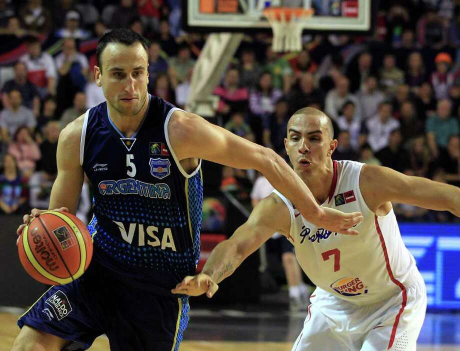 Argentina's Manu Ginobili, left, dribbles past Puerto Rico's Carlos Arroyo during a FIBA Americas Championship basketball game in Mar del Plata, Argentina, Friday, Sept. 2, 2011. The top two finishers of the tournament get an automatic berth in the 2012 London Olympics and the next three advance to the last-chance Olympic qualifier to be held in July 2012. Photo: Martin Mejia/Associated Press