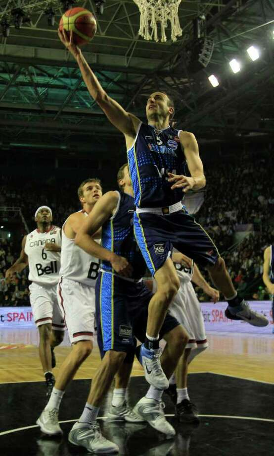 Argentina's Manu Ginobili, top, goes up for a shot during a FIBA Americas Championship basketball game Canada in Mar del Plata, Argentina, Monday, Sept. 5, 2011. The top two finishers of the tournament get an automatic berth in the 2012 London Olympics and the next three advance to the last-chance Olympic qualifier to be held in July 2012. Photo: Martin Mejia/Associated Press