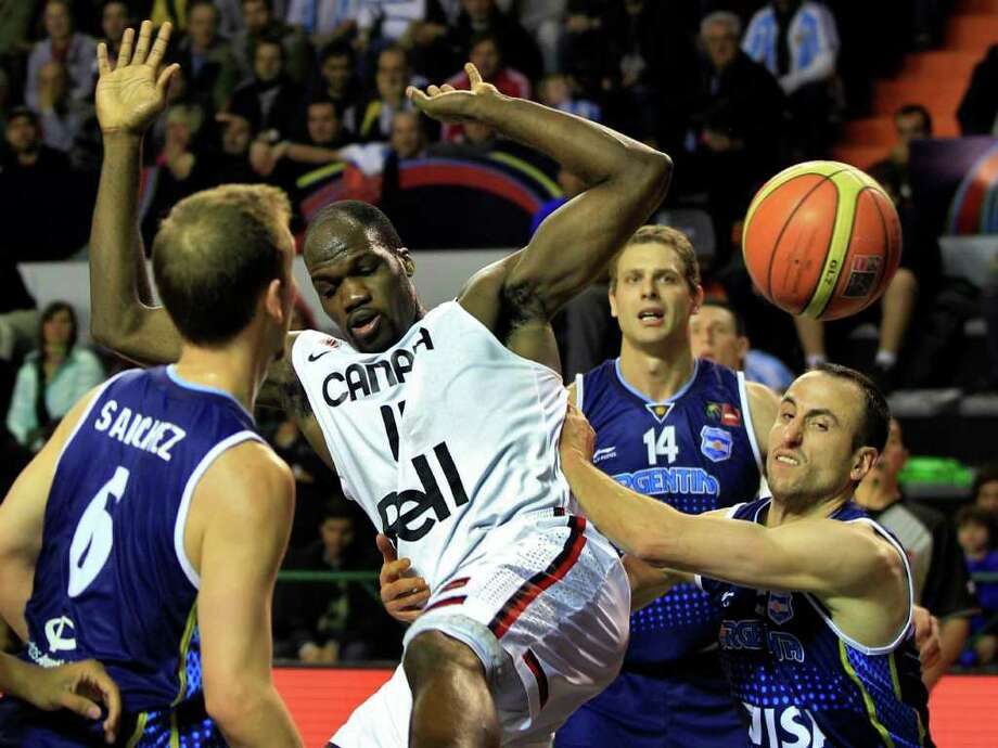 Canada's Joel Anthony, center, is grabbed by Argentina's Manu Ginobili, right, as Argentina's Juan Sanchez, left, looks on during a FIBA Americas Championship basketball game in Mar del Plata, Argentina, Monday, Sept. 5, 2011. The top two finishers of the tournament get an automatic berth in the 2012 London Olympics and the next three advance to the last-chance Olympic qualifier to be held in July 2012. Photo: Martin Mejia/Associated Press