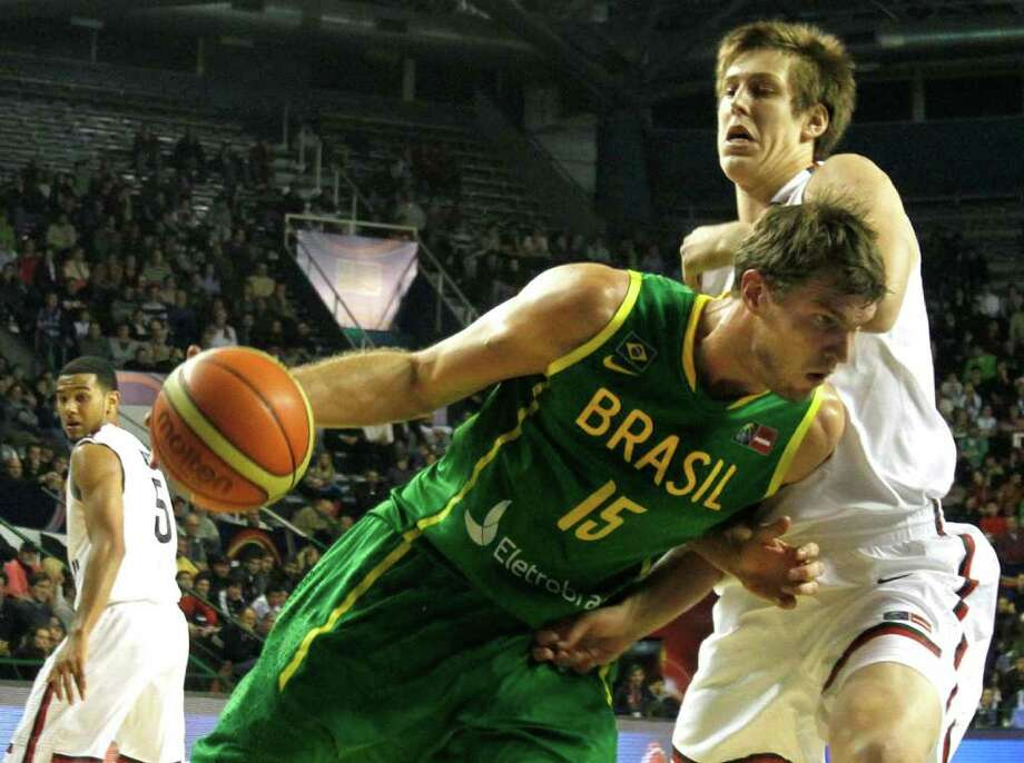 Brazil's Tiago Splitter, left, dribbles past Canada's Kelly Olynky during a FIBA Americas Championship basketball game in Mar del Plata, Argentina, Wednesday, Aug. 31, 2011. The top two finishers of the tournament get an automatic berth in the 2012 London Olympics and the next three advance to the last-chance Olympic qualifier to be held in July 2012. Photo: Martin Mejia/Associated Press