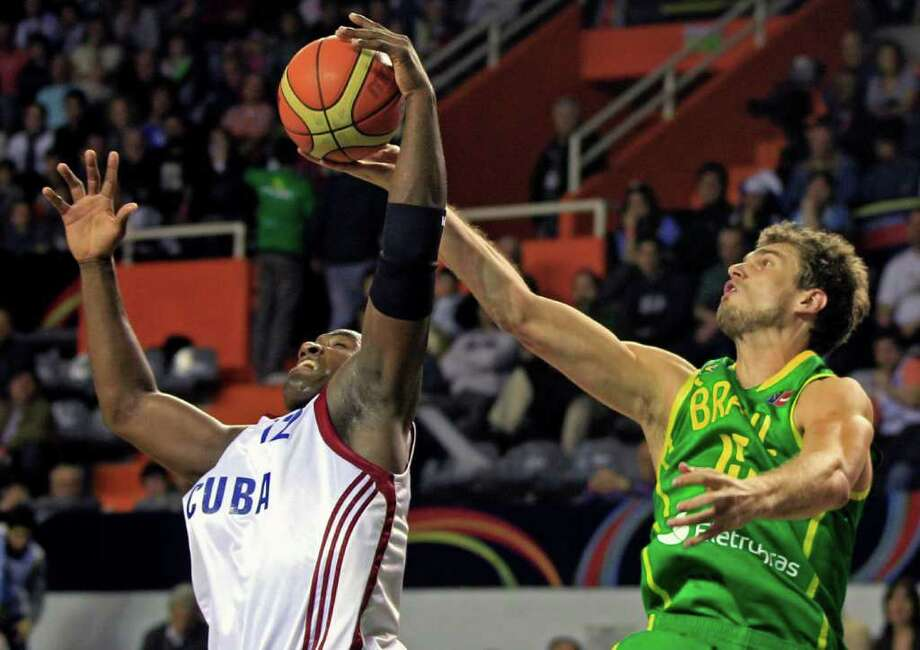 Brazil's Tiago Splitter, right, and Cuba's Yoan Luis battle for possession of the ball during a FIBA Americas Championship basketball game in Mar del Plata, Argentina, Saturday Sept. 3, 2011. The top two finishers of the tournament get an automatic berth in the 2012 London Olympics and the next three advance to the last-chance Olympic qualifier to be held in July 2012. Photo: Martin Mejia/Associated Press