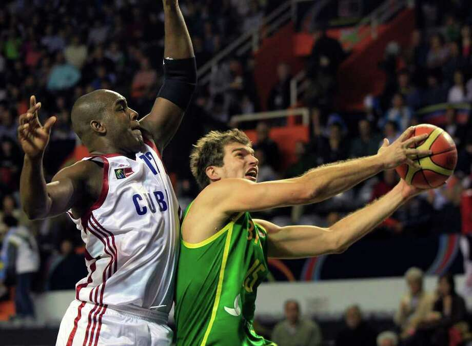 Brazil's Tiago Splitter, right, goes to the basket against Cuba's Yoan Luis during a FIBA Americas Championship basketball game in Mar del Plata, Argentina, Saturday, Sept. 3, 2011. The top two finishers of the tournament get an automatic berth in the 2012 London Olympics and the next three advance to the last-chance Olympic qualifier to be held in July 2012. Photo: Martin Mejia/Associated Press