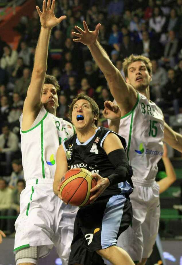 Uruguay's Fernando Martinez, center, goes for a shot against Brazil's players Guilherme Giovannoni, left, and Tiago Splitter during a FIBA Americas Championship basketball game in Mar del Plata, Argentina, Monday, Sept. 5, 2011. The top two finishers of the tournament get an automatic berth in the 2012 London Olympics and the next three advance to the last-chance Olympic qualifier to be held in July 2012. Photo: Martin Mejia/Associated Press