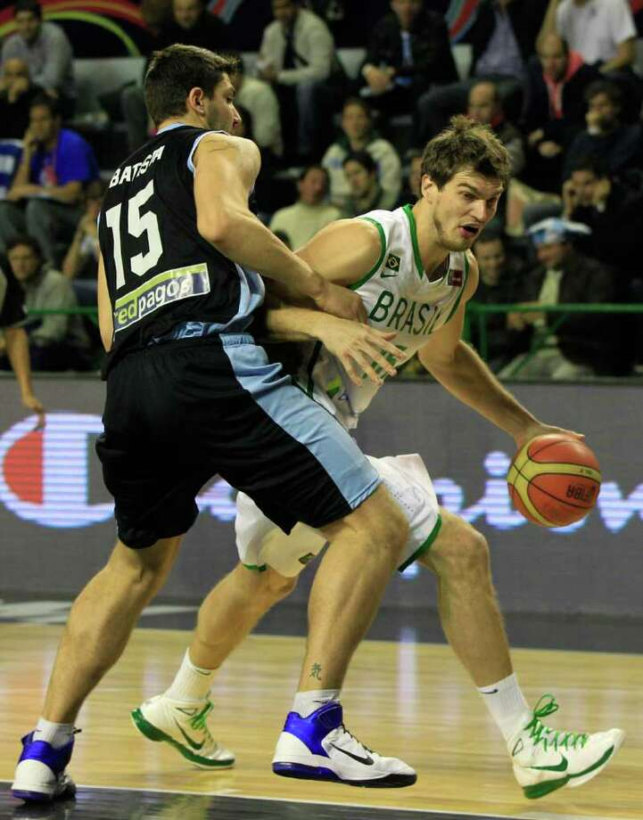 Brazil's Tiago Splitter, right, dribbles past Uruguay's Esteban Batista during a FIBA Americas Championship basketball game in Mar del Plata, Argentina, Monday, Sept. 5, 2011. The top two finishers of the tournament get an automatic berth in the 2012 London Olympics and the next three advance to the last-chance Olympic qualifier to be held in July 2012. Photo: Martin Mejia/Associated Press