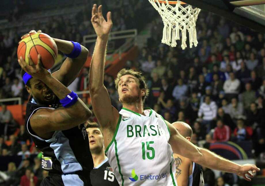 Uruguay's Reque Newsome, left, is blocked by Brazil's Tiago Splitter during a FIBA Americas Championship basketball game in Mar del Plata, Argentina, Monday, Sept. 5, 2011. The top two finishers of the tournament get an automatic berth in the 2012 London Olympics and the next three advance to the last-chance Olympic qualifier to be held in July 2012. Photo: Martin Mejia/Associated Press
